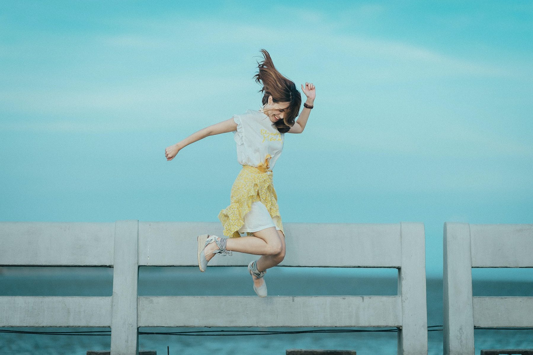 the sunny side to low self belief woman in white dress jumping happy